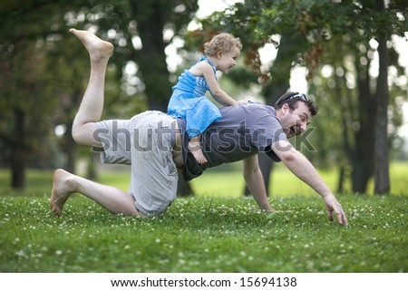 Happy young father play with his small three years old daughter in the garden - stock photo