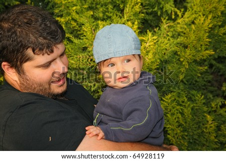 Happy young father playing with his little son in a pine park - stock photo