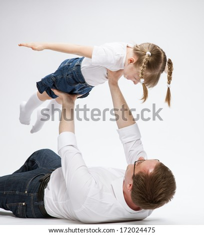 Happy young father playing with his smiling daughter, neutral background - stock photo