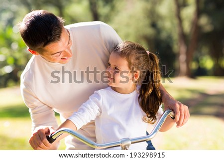 happy young father riding bicycle with his daughter outdoors - stock photo