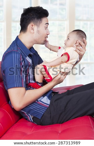Happy young father sitting on the sofa while holding his baby, shot in the living room at home - stock photo