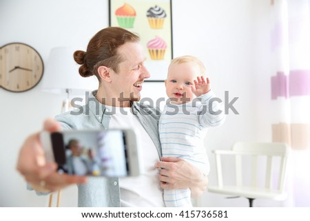 Happy young father taking a selfie with his baby, close up - stock photo