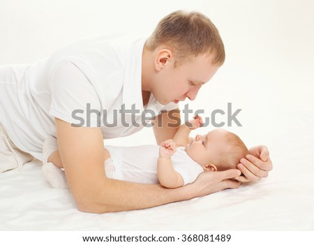 Happy young father with baby on bed at home