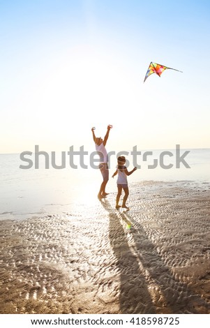 Happy young father with daughter with flying a kite on the beach. Holiday concept