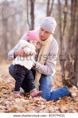 happy young father with his daughter spending time outdoor in the autumn park and teaching her to walk - stock photo