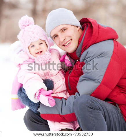 happy young father with his daughter spending time outdoor in the winter park - stock photo