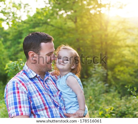 Happy young father with little baby daughter outdoors - stock photo