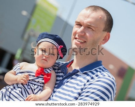 Happy young father with little daughter clothing with stripes, outdoors - stock photo