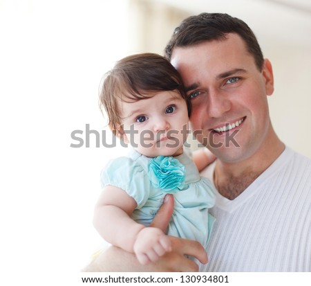 Happy young father with little daughter indoors - stock photo