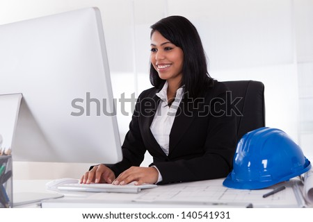 Happy Young Female Architect Using Computer In Office - stock photo