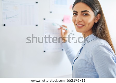 Happy young female business woman or teacher writing on white board with erasable marker