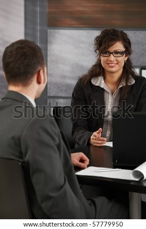 Happy young female candidate smiling to businessman during job interview.? - stock photo