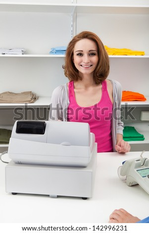 Happy Young Female Cashier With Cash Register At Cash Counter - stock photo