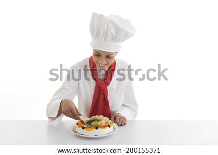 Happy young female chef making mixed fruit cake isolated over white background
