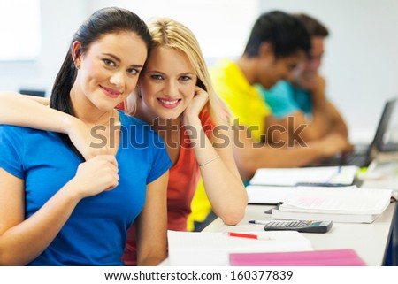 happy young female college friends in lecture room - stock photo