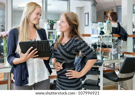 Happy young female customer looking at hairdresser while holding digital tablet - stock photo