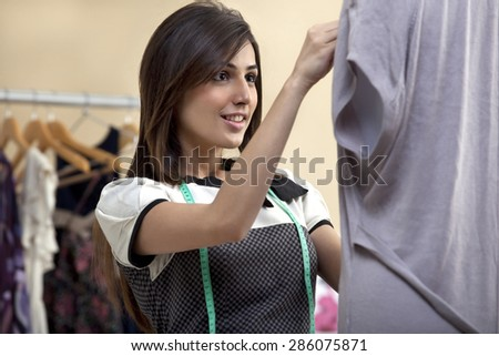 Happy young female designer fixing dress on mannequin - stock photo