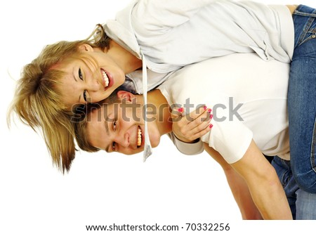 Happy young female enjoying a piggyback ride on boyfriends back against white