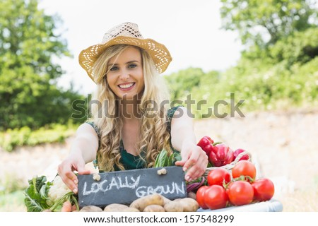 Happy young female farmer standing at her stall at the farmers market smiling at the camera - stock photo