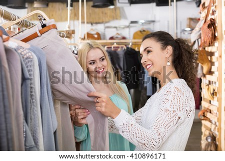 Happy young female friends choosing trousers in shop and smiling