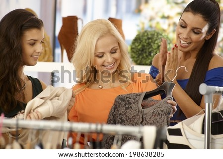 Happy young female friends shopping together at clothes store. - stock photo