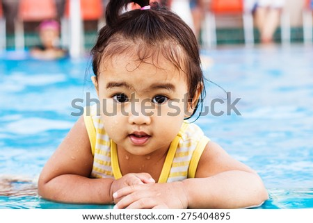 Happy young female girl child baby relaxing on the side of a swimming pool