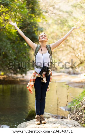 happy young female hiker arms open in mountain valley - stock photo