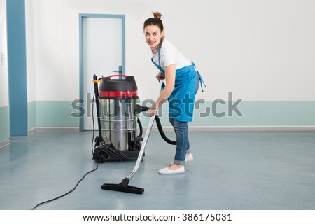 Happy Young Female Janitor Cleaning Floor With Vacuum Cleaner