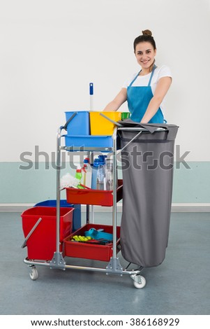 Happy Young Female Janitor With Cleaning Equipment - stock photo