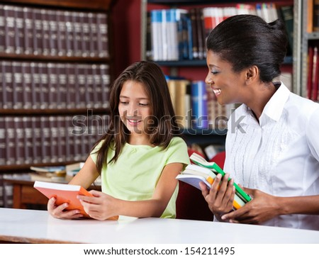 Happy young female librarian and schoolgirl looking together at book in library - stock photo