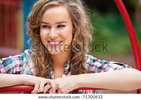 Happy young female looking away and smiling outdoors - stock photo