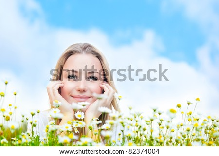Happy young female lying on the flower field, over blue cloudy sky, with copy space, leisure, fun and wellness concept