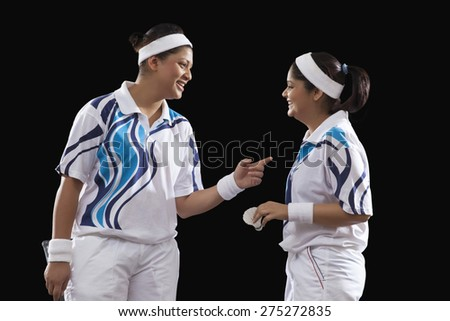 Happy young female players communicating with each other isolated over black background - stock photo
