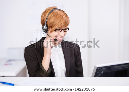 Happy young female receptionist speaking on headphones while looking at computer at desk