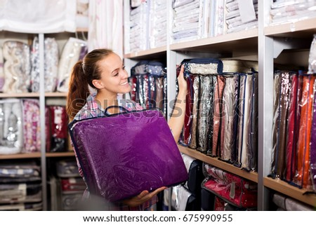 Happy young female shopper searching for bed linen in textile shop