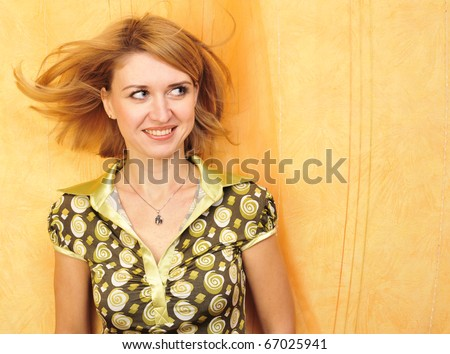 Happy young female standing relaxed by the wall on the floor - stock photo