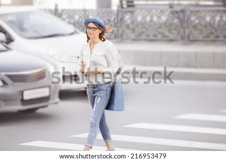 Happy young female student crossing the street with a coffee-to-go cup, smiling happily against urban city background. - stock photo