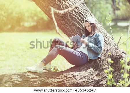 Happy young female student is reading in a park. She is sitting on a tree and enjoying her book. - stock photo