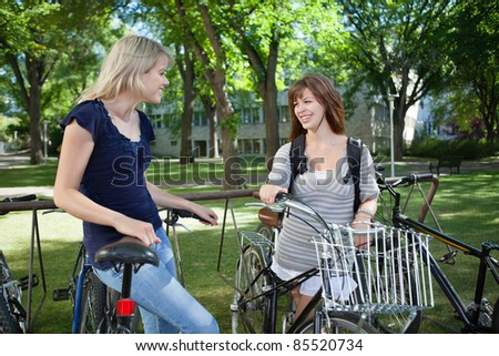 Happy young female students standing with bicycle at college campus lawn