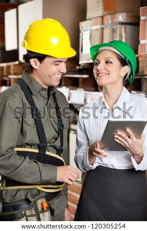 Happy young female supervisor with digital tablet and foreman at warehouse