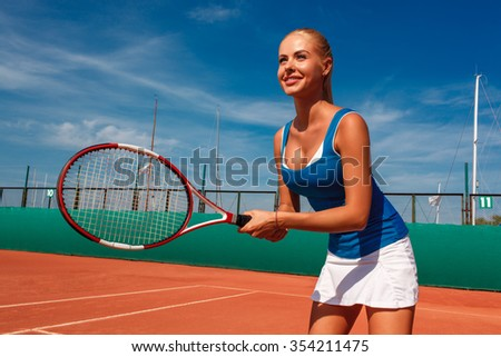 happy young female tennis player posing with racket on a tennis court outdoors - stock photo