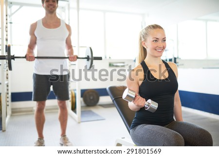 Happy Young Fit Couple Lifting Barbells While Looking at theirselves on the Mirror Inside the Gym - stock photo
