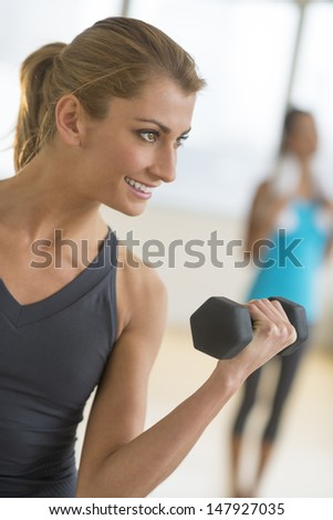 Happy young fit woman lifting dumbbell at health club - stock photo