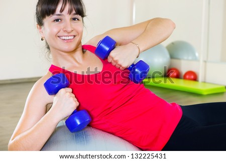Happy young fitness woman during workout with dumbbells - stock photo