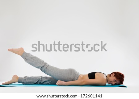happy young fitness woman exercising with her legs - stock photo