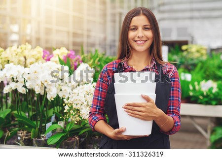 Happy young florist working in a hothouse tending to the exotic tropical orchids re-potting and transplanting them smiling at the camera with flowerpots on her hands - stock photo