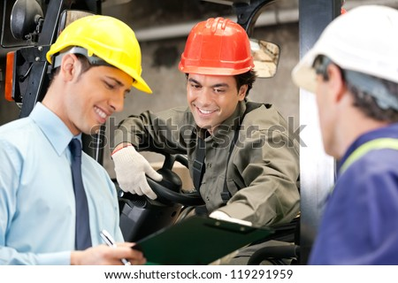 Happy young forklift driver with supervisor holding clipboard at warehouse - stock photo
