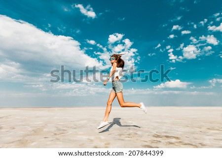 Happy young fresh Slim athletic girl runs along the beach in trendy jeans shorts and white sneakers. Blue sky in the clouds, summer sunny mood. - stock photo