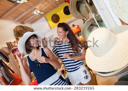 Happy,  young friends choosing a perfect hat for them.Shopping theme - stock photo
