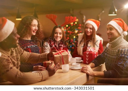 Happy young friends congratulating each other on Christmas evening - stock photo